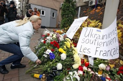 A woman leaves flowers outside the French Embassy in Kiev on November 14, 2015, to pay tribute to the victims of the deadly attacks in Paris. Islamic State jihadists on Saturday claimed a series of coordinated attacks by suicide bombers and gunmen in Paris that killed at least 128 people at a concert hall, restaurants and the national sports stadium. AFP PHOTO / YURIY KIRNICHNY